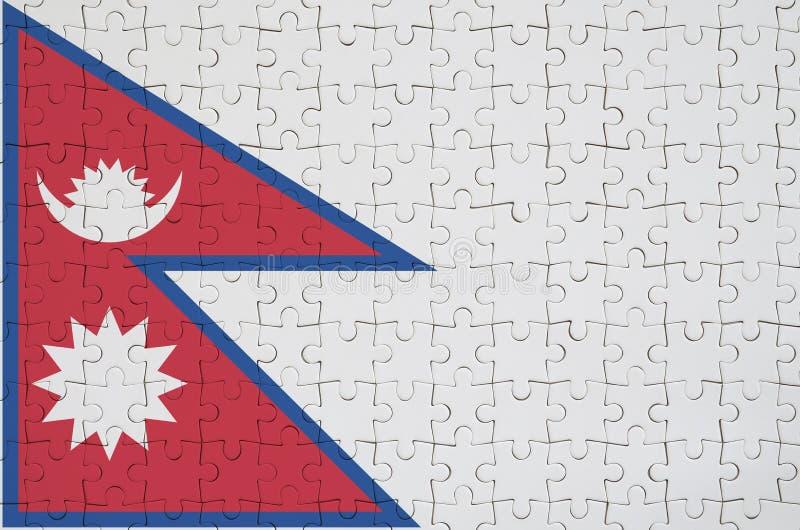 Флаг Непала показан на сложенной головоломке стоковая фотография