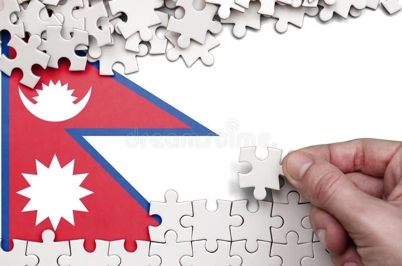 Флаг Непала показан на таблице на которой человеческая рука складывает головоломку белого цвета стоковая фотография rf