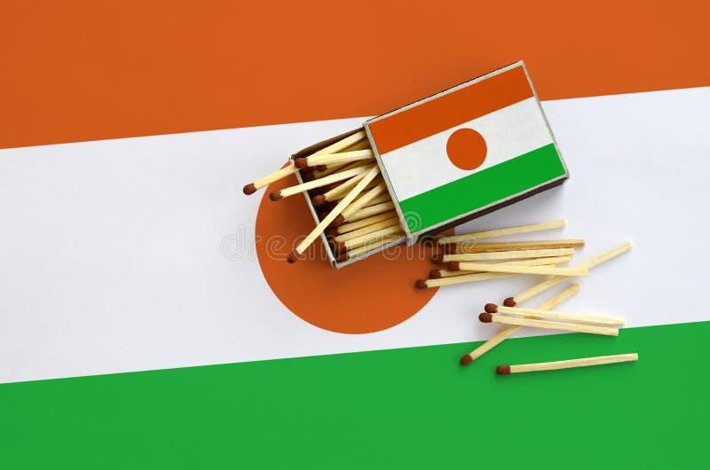 Флаг Нигера показан на открытом matchbox, от которого несколько спичек падают и лож на большом флаге стоковое изображение rf