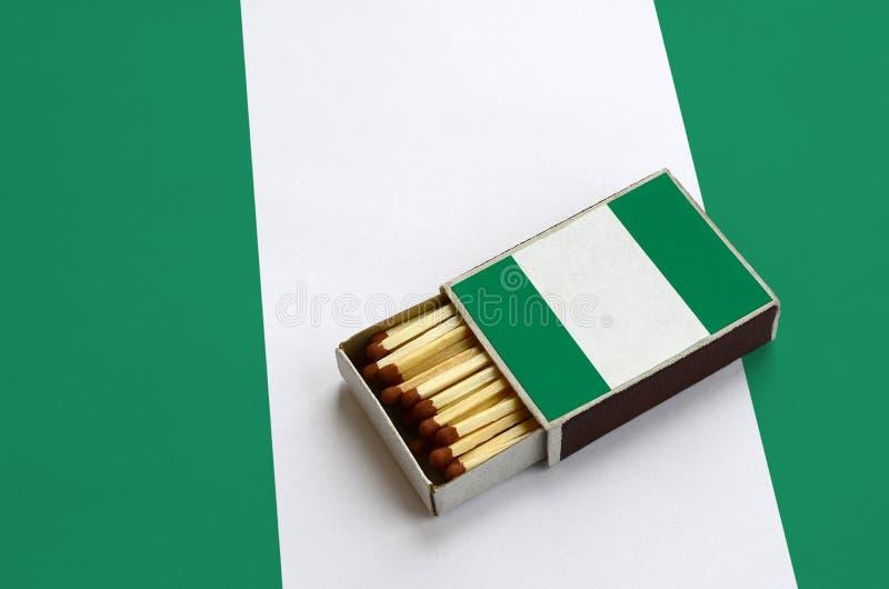 Флаг Нигерии показан в открытом matchbox, который заполнен с спичками и лежит на большом флаге стоковое фото rf