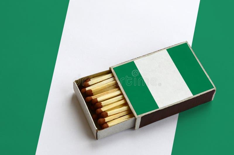 Флаг Нигерии показан в открытом matchbox, который заполнен с спичками и лежит на большом флаге стоковые изображения rf