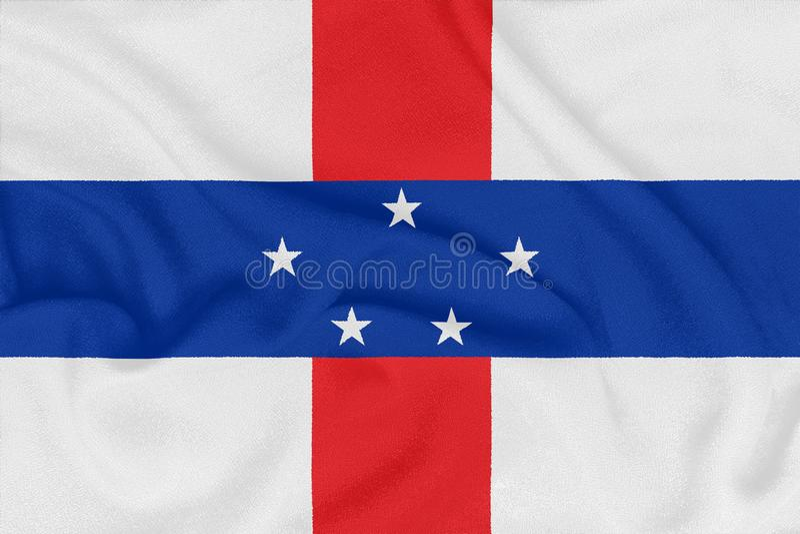 Флаг Нидерландские Антильские острова на текстурированной ткани Патриотический символ стоковая фотография