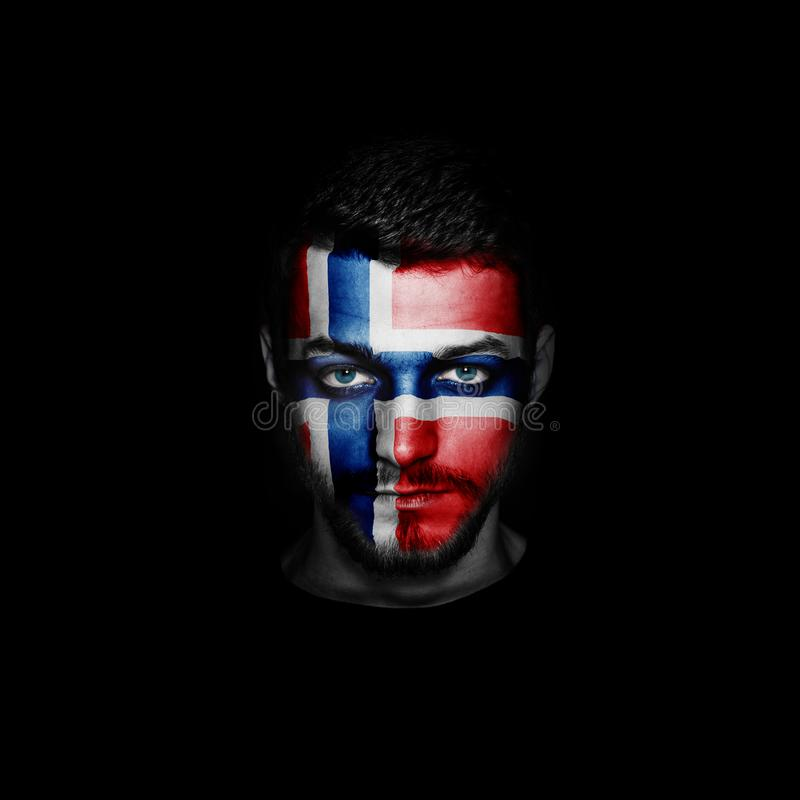 Флаг Норвегии покрасил на стороне человека стоковое фото
