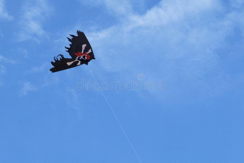 Флаг пирата змея в голубом небе с белыми облаками стоковая фотография rf