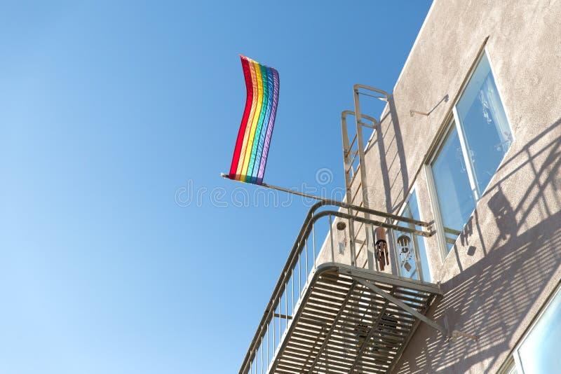 Флаг радуги гей-парада развевая на балконе здания стоковая фотография