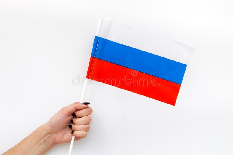 Флаг России в руке на белом взгляде сверху предпосылки стоковое изображение