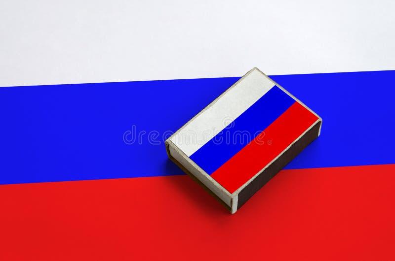 Флаг России изображен на matchbox который лежит на большом флаге стоковое фото rf