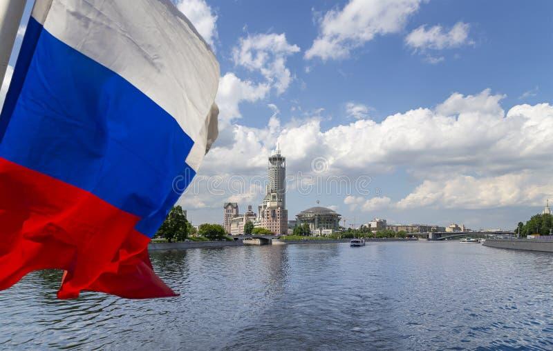 Флаг России и дом концертного зала музыки на банках реки Москвы r стоковые изображения