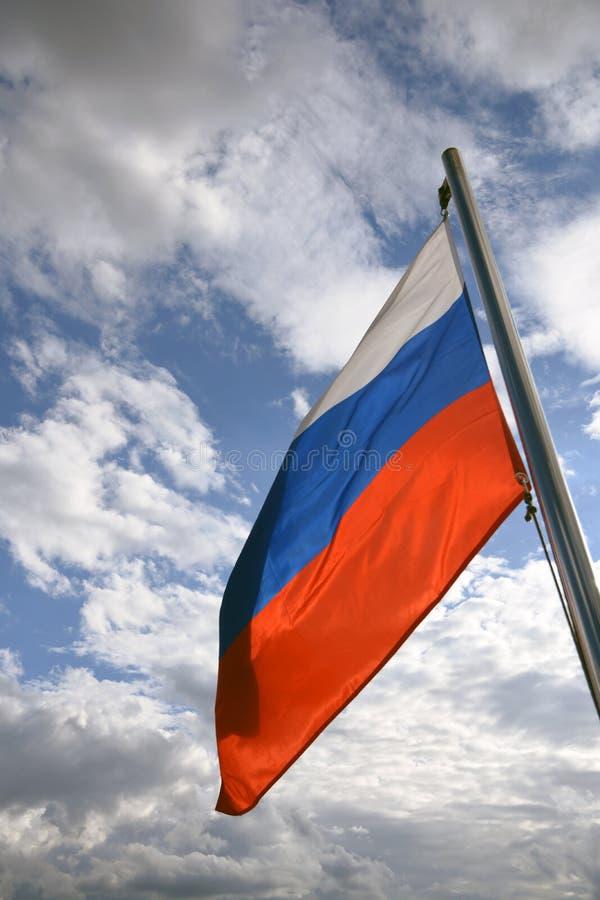 Флаг России на голубом небе с предпосылкой облаков стоковое изображение rf