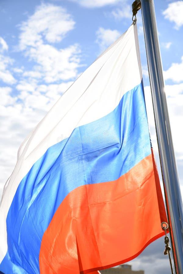Флаг России на голубом небе с предпосылкой облаков стоковые изображения