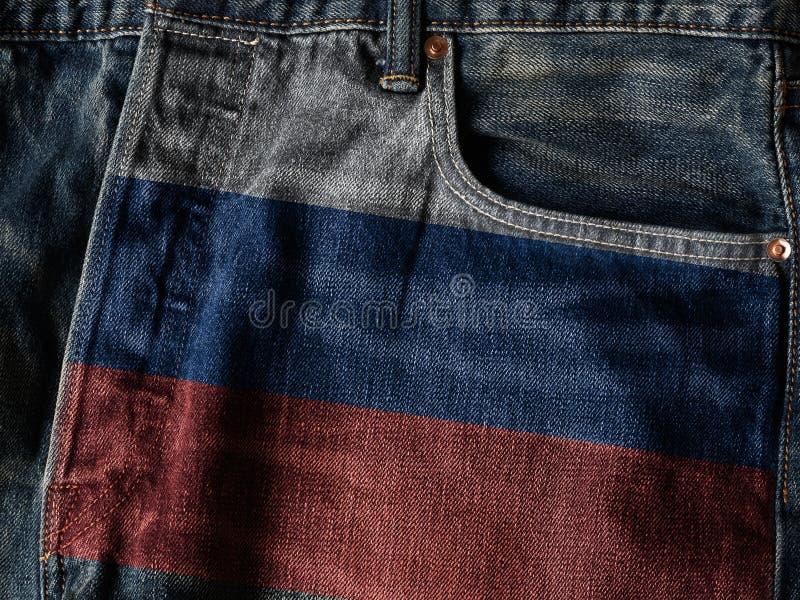 Флаг России на текстуре джинсовой ткани джинсов с словом гордости против как крюка hang долларов принципиальной схемы приманки пр стоковое фото