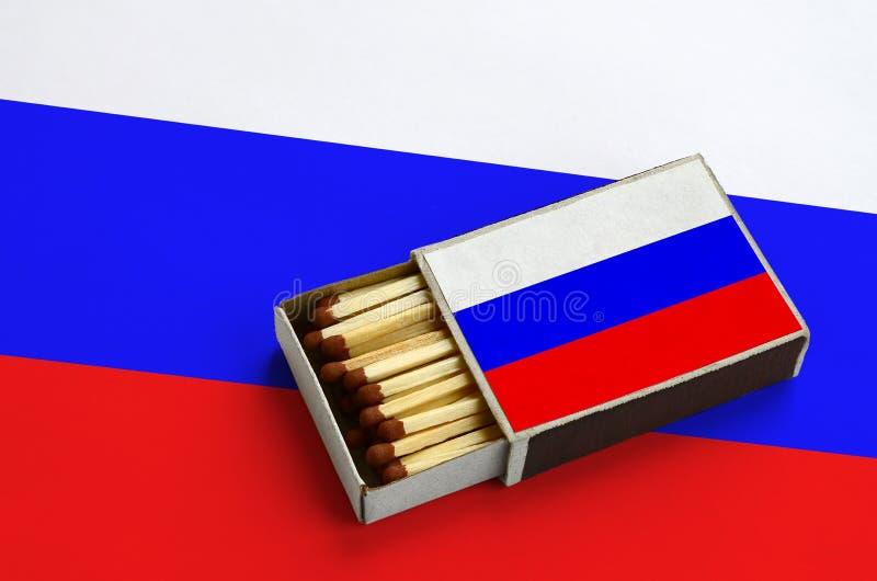 Флаг России показан в открытом matchbox, который заполнен с спичками и лежит на большом флаге стоковое изображение