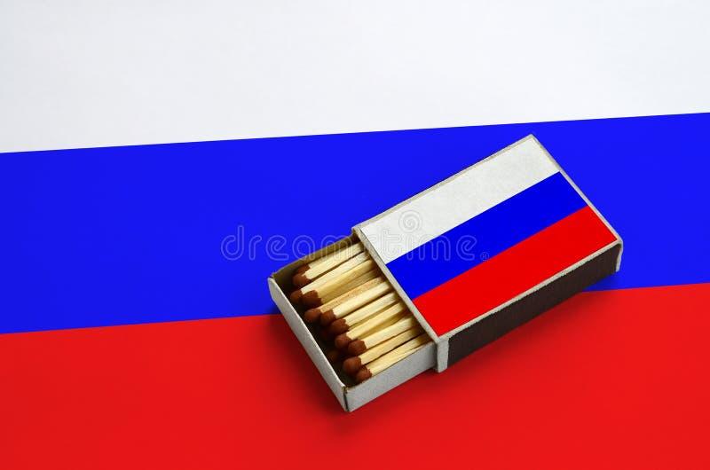 Флаг России показан в открытом matchbox, который заполнен с спичками и лежит на большом флаге стоковые изображения