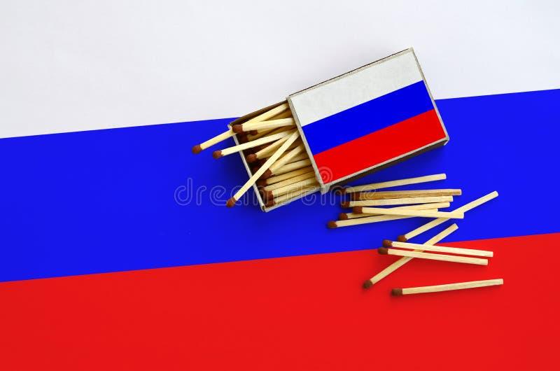 Флаг России показан на открытом matchbox, от которого несколько спичек падают и лож на большом флаге стоковое изображение
