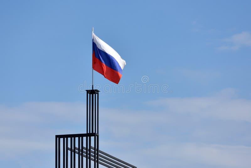Флаг России против голубого неба с ветром стоковые изображения