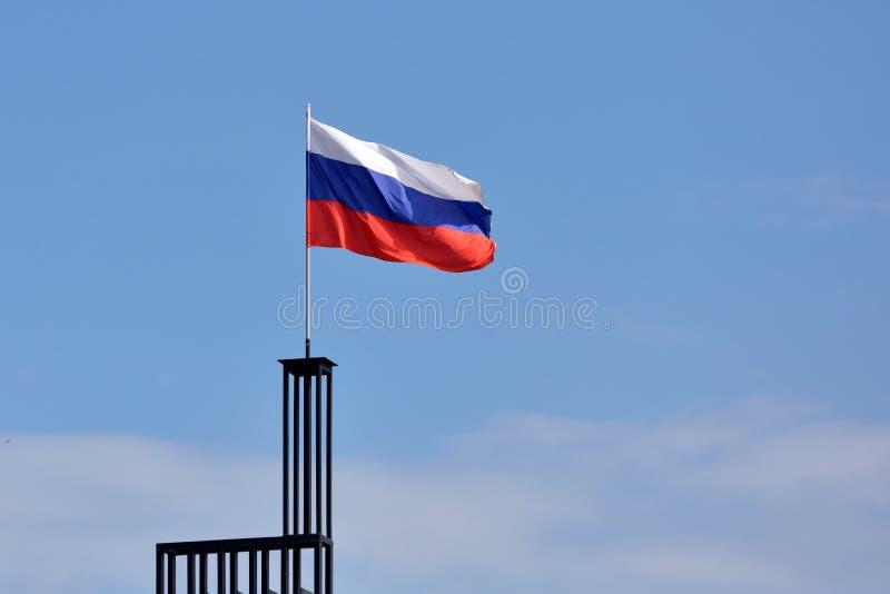 Флаг России против голубого неба с ветром стоковая фотография