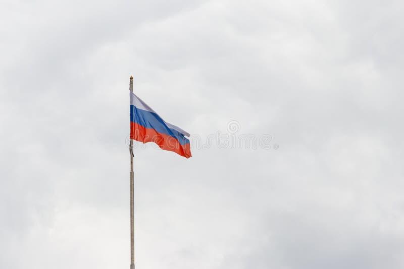 Флаг России против хмурого облачного неба стоковое фото