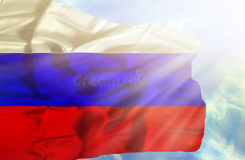 Флаг России развевая против голубого неба с sunrays стоковое фото rf