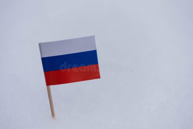 Флаг России сделанный от бумаги с коричневой зубочисткой на белой предпосылке снега стоковая фотография rf
