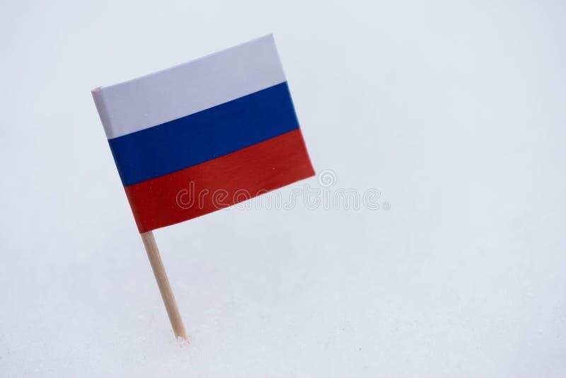 Флаг России сделанный от бумаги с коричневой зубочисткой на белой предпосылке снега стоковые изображения