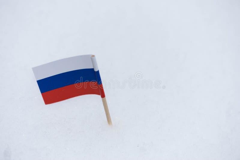 Флаг России сделанный от бумаги с коричневой зубочисткой на белой предпосылке снега стоковые фотографии rf