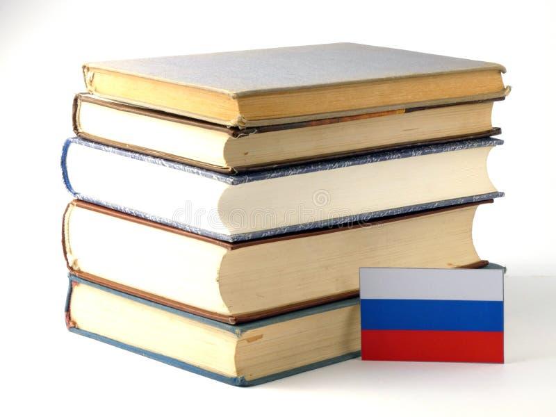 Флаг России с кучей книг на белой предпосылке стоковые изображения