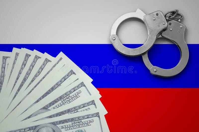 Флаг России с наручниками и пачка долларов Концепция противозаконной деятельности банка в валюте США стоковые фото