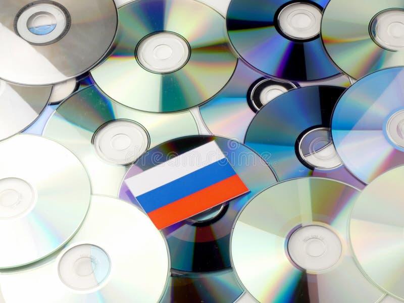 Флаг России na górze кучи КОМПАКТНОГО ДИСКА и DVD изолированной на белизне стоковые изображения rf