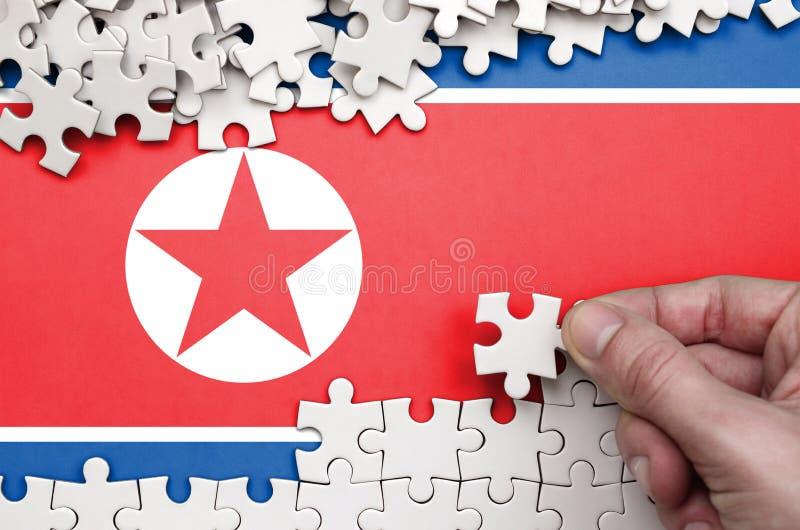 Флаг Северной Кореи показан на таблице на которой человеческая рука складывает головоломку белого цвета стоковые фотографии rf