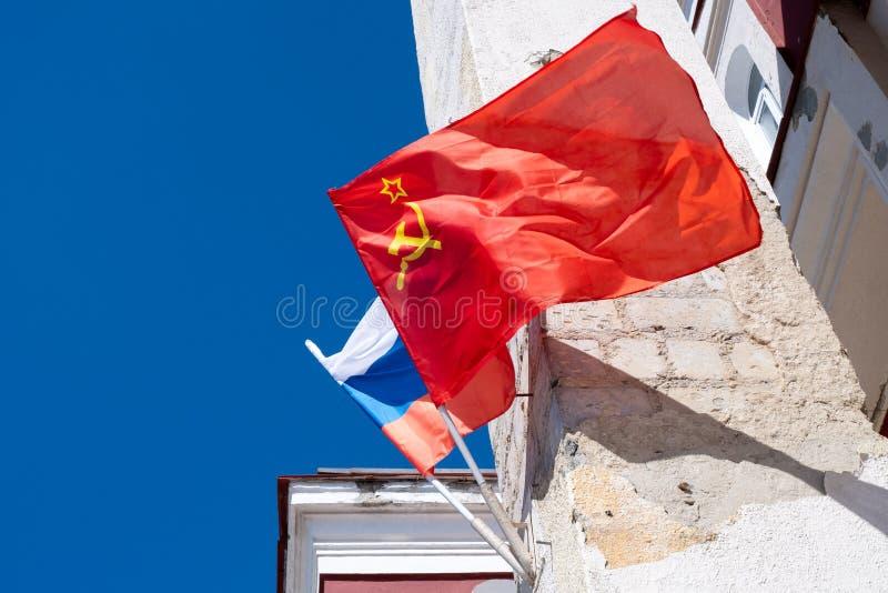 Флаг СССР и флаг России на стене старого здания под голубым небом стоковые фотографии rf