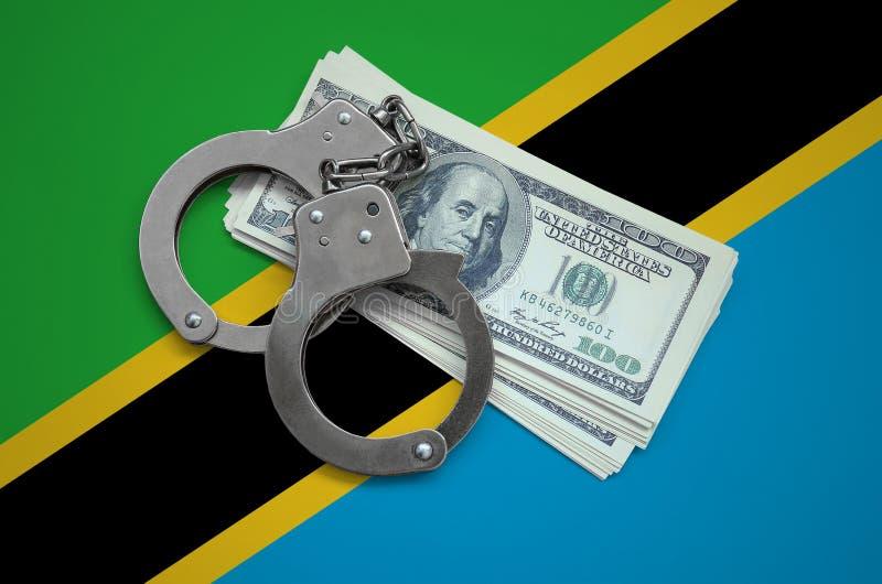 Флаг Танзании с наручниками и пачка долларов Коррупция валюты в стране финансовые злодеяния стоковая фотография