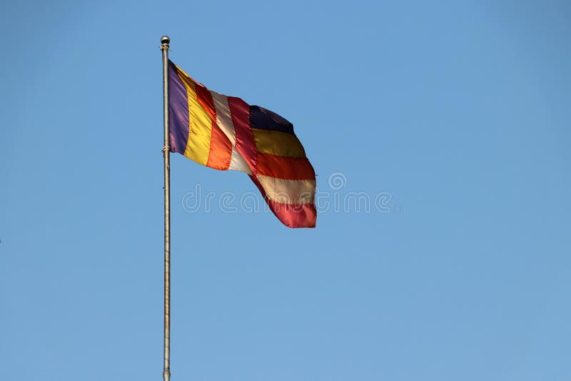 Флаг ткани буддийский дунутый ветром на флагштоке с предпосылкой голубого неба стоковое фото rf
