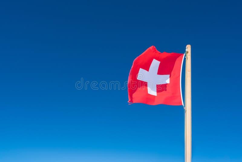 Флаг Швейцарии на фоне голубого неба Верхняя часть Jungfrau стоковое изображение