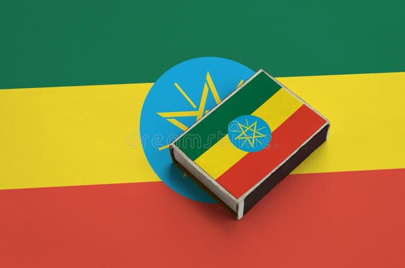 Флаг Эфиопии изображен на matchbox который лежит на большом флаге стоковые изображения