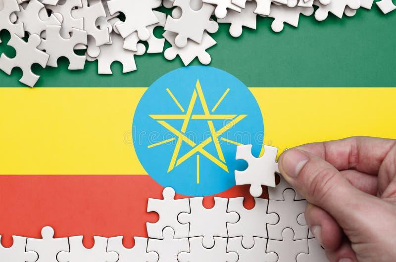 Флаг Эфиопии показан на таблице на которой человеческая рука складывает головоломку белого цвета стоковые фото
