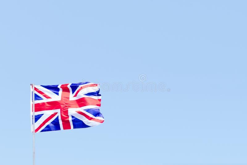 Флаг Юниона Джек Великобритании Великобритании дуя в ветре против пустого голубого неба стоковая фотография