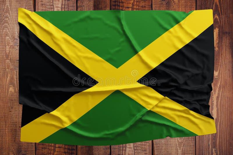 Флаг Ямайки на предпосылке деревянного стола Сморщенный ямайский взгляд сверху флага стоковая фотография rf
