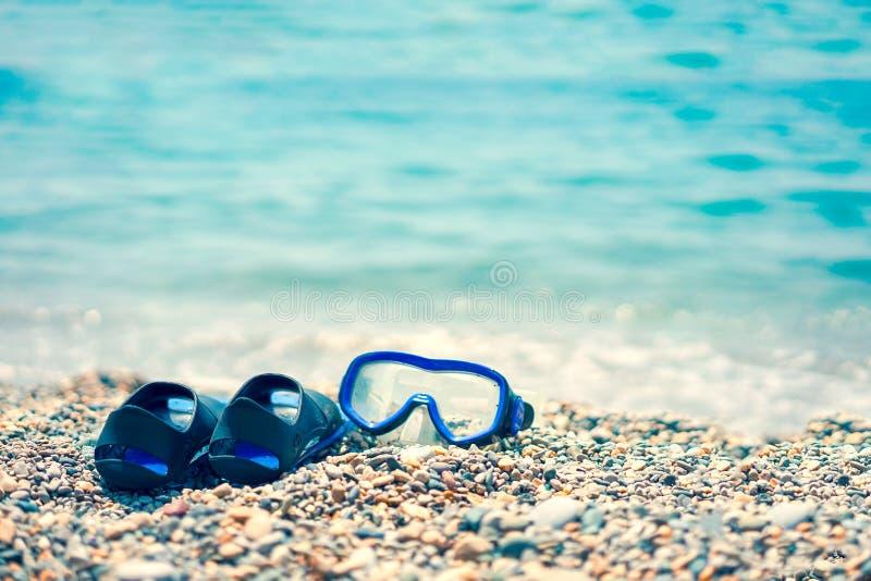Флипперы и мускус шноркеля на камешках на морском побережье стоковые изображения