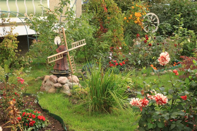 Флористическая лужайка с декоративной ветрянкой стоковые фотографии rf