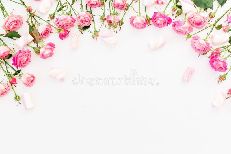 Флористическая рамка сделанная из розовых роз и зефира на белизне Плоское положение, взгляд сверху стоковое изображение rf