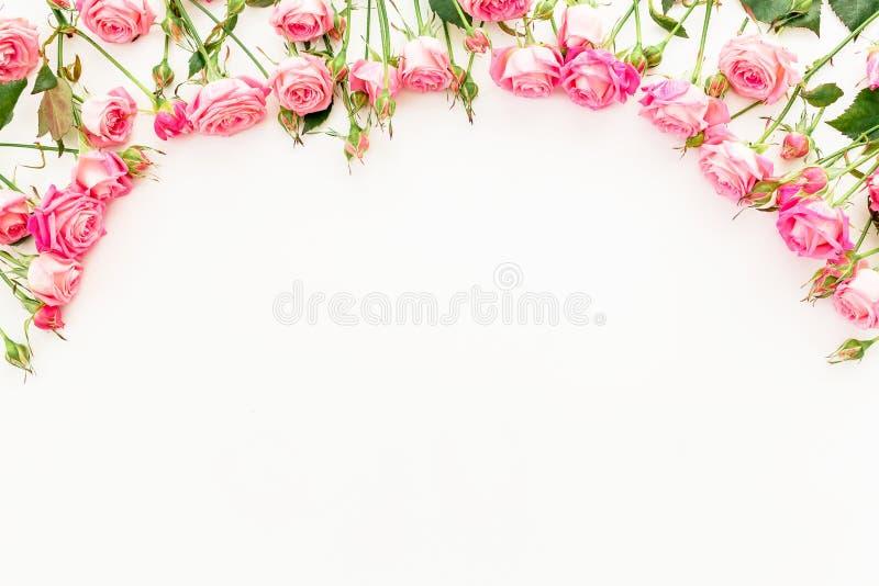 Флористическая рамка сделанная розовых роз на белой предпосылке Плоское положение, взгляд сверху стоковые фотографии rf