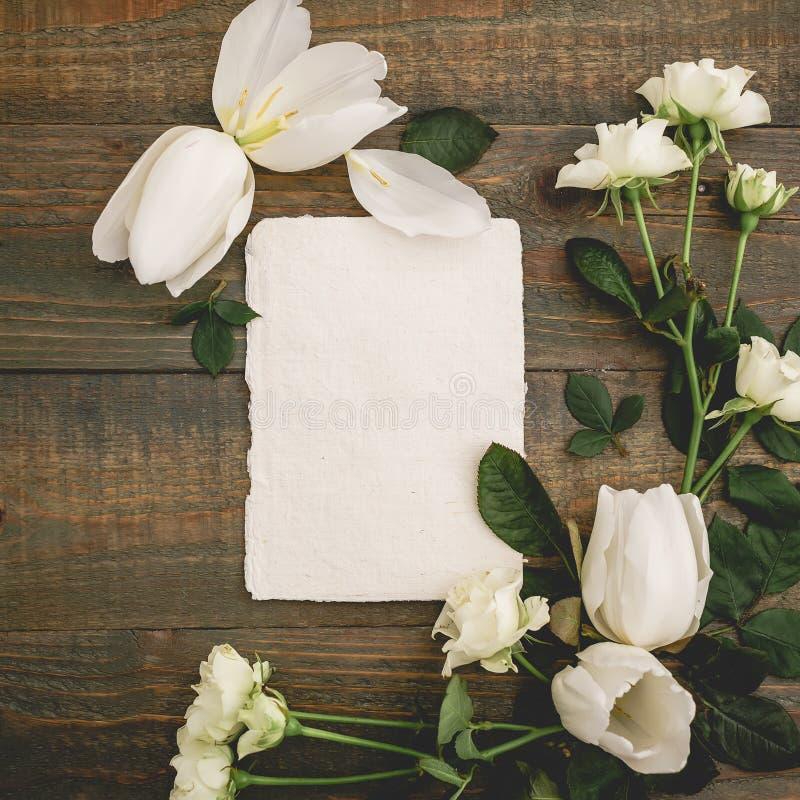 Флористический состав с бумажной карточкой, белыми тюльпанами и розами на деревянной предпосылке Плоское положение, взгляд сверху стоковое фото rf
