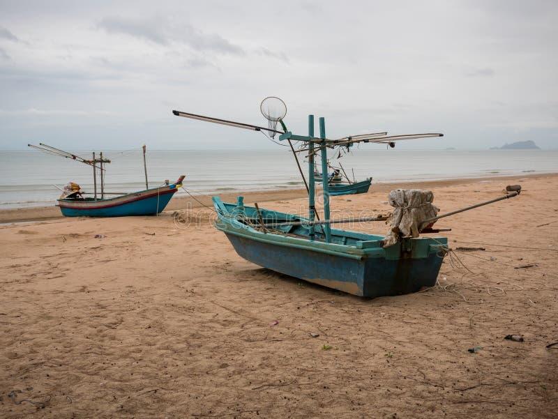 Флот рыбацких лодок кальмара на пляже в пасмурном дне утра, с предпосылкой моря стоковые изображения rf
