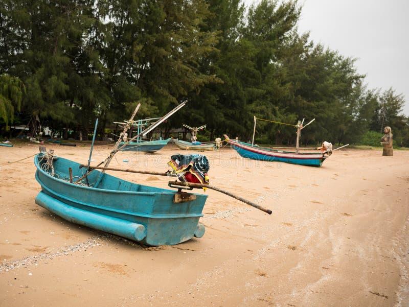 Флот рыбацких лодок кальмара на пляже в пасмурном дне утра, с предпосылкой моря стоковые изображения