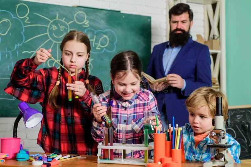 Фокусировать на работе делать эксперименты с жидкостями в химической лаборатории дети делая эксперименты по науки E r стоковое изображение rf