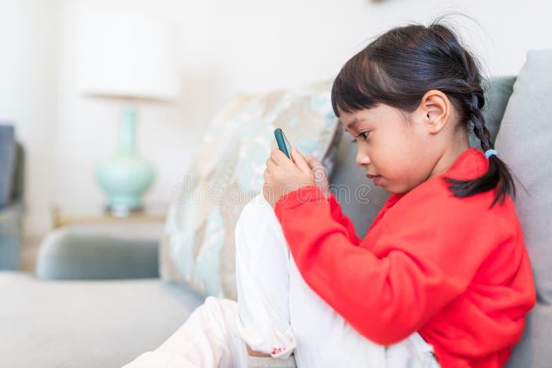 Фокус маленькой девочки на мобильном телефоне стоковые изображения