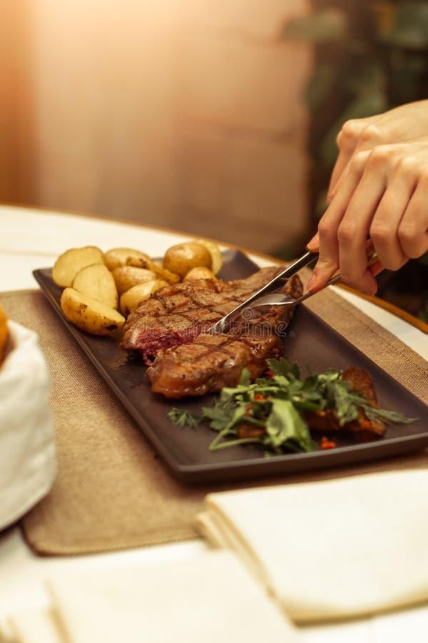 Фокус на мясе где вилка и нож Красивые женские руки в ресторане на стейке striploin говядины отрезка таблицы стоковое изображение rf