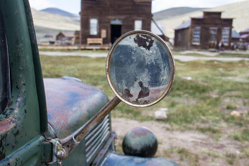 Фокус на старом классическом зеркале заднего вида на классической тележке jalopy, получившейся отказ в город-привидении Bodie в К стоковое изображение rf