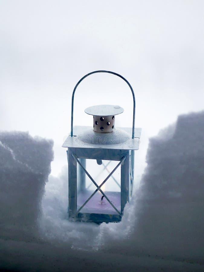 Фонарик с горящей свечой в снеге против фона ландшафта зимы, плохой погоды стоковые фото