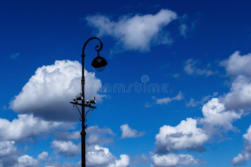Фонарик с громкоговорителем на предпосылке облаков стоковое изображение